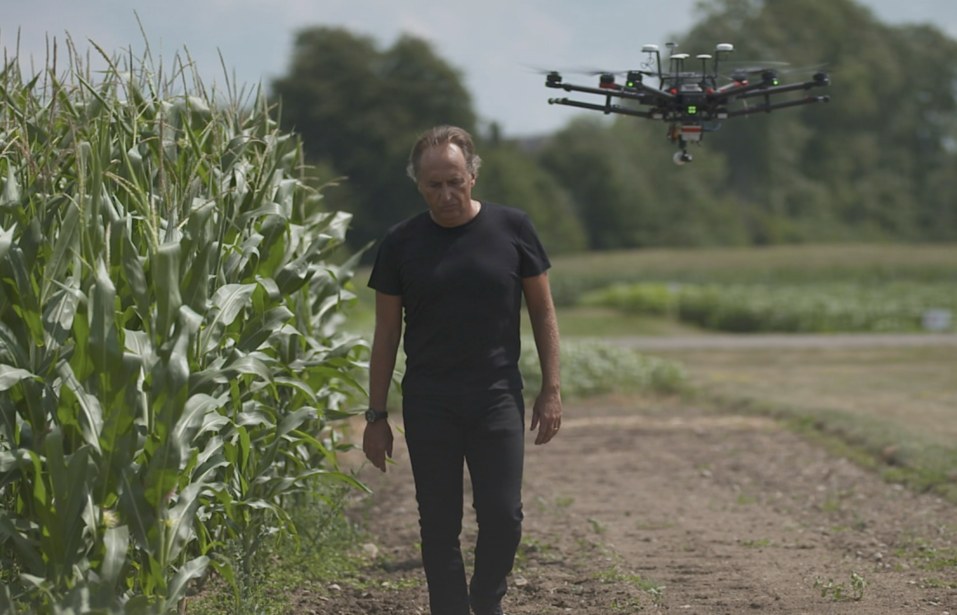 Bruno Basso walks in field with drone