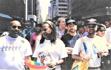 Moore at his first ever PRIDE March in NYC walking in a large group of people.