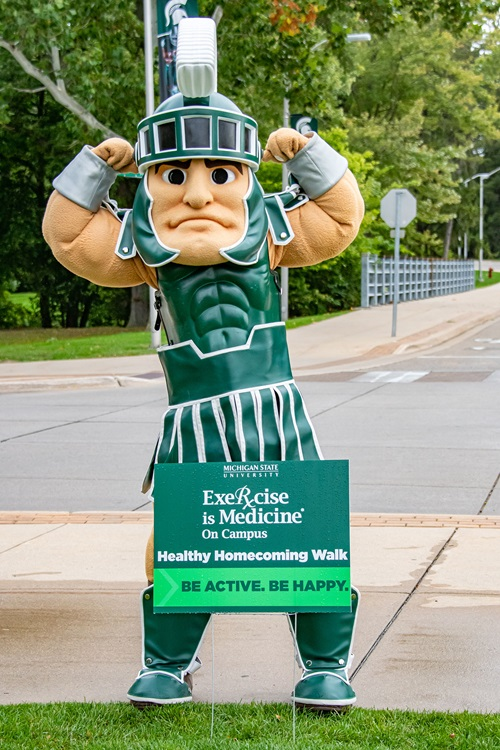 The Sparty mascot behind a sign which reads