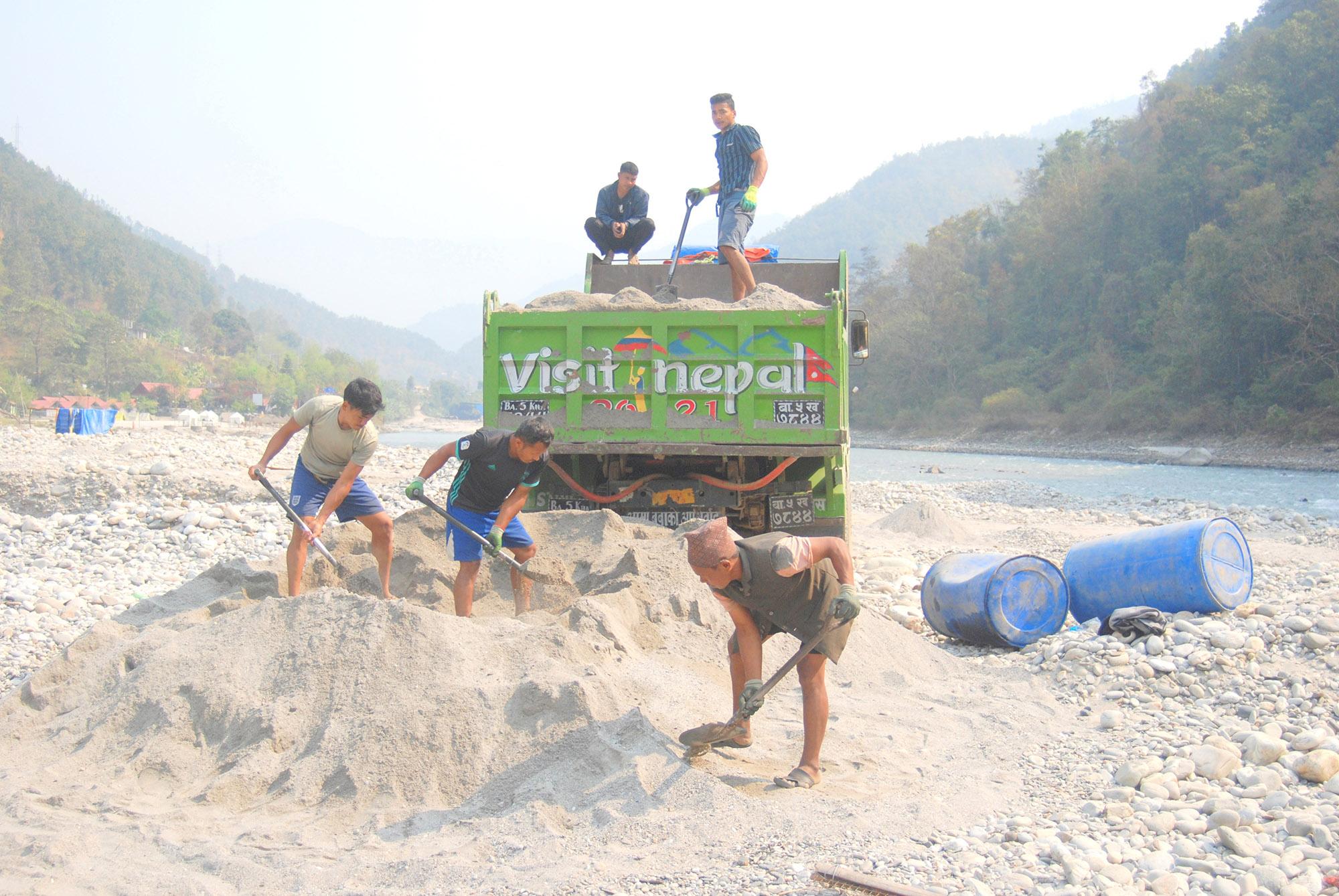 Homens carregando areia de um poço em Sunkoshi, perto de Kathmandu, no Nepal